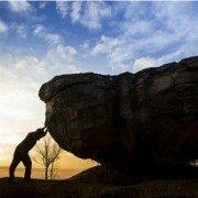 Mand støtter en stor sten med solnedgang i baggrunden - Mand med selvtillid
