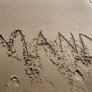 Mand skrevet i sandet på en strand